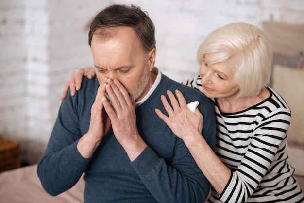 Страдает аллергией. старшая жена поддерживает своего пожилого мужа, закрывая лицо во время чихания.