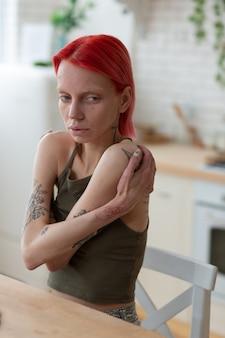 Страдает анорексией. молодая рыжеволосая женщина страдает анорексией, касаясь ее плеч