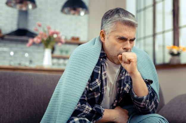 風邪にかかっている。風邪に苦しんでいる間彼の手に咳をする不幸な元気のない男