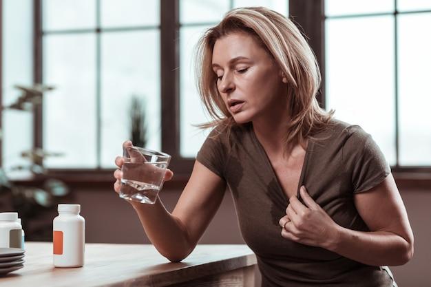うつ病に苦しんでいます。薬を服用した後に水を飲むうつ病に苦しんでいる金髪のストレスの多い女性