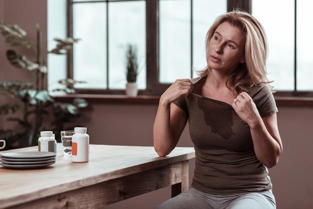 発熱に苦しんでいます。落ち込んで病気の金髪の女性が熱にひどく苦しんでいる