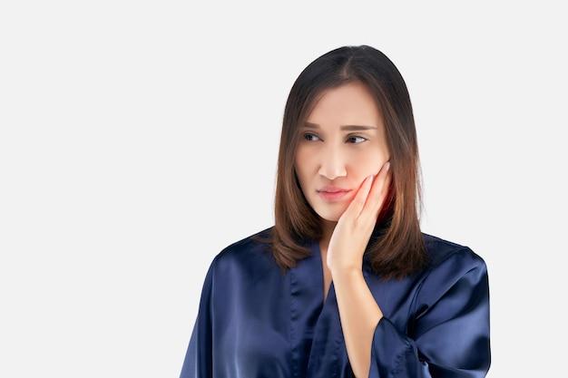 Страдает от зубной боли. красивая молодая женщина страдает от зубной боли, стоя на сером фоне