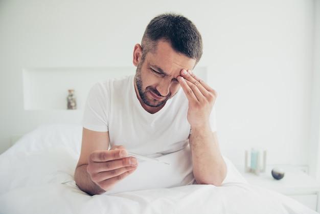 Страдающий парень позирует в своей постели