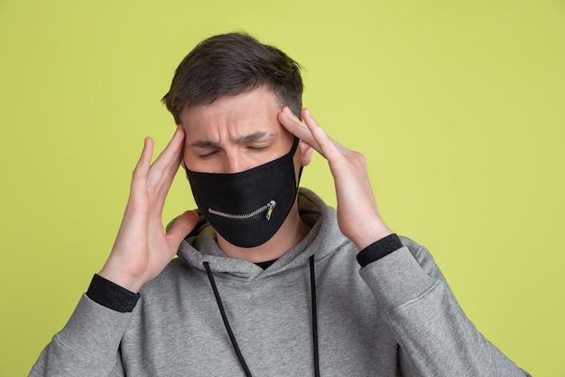 두통의 고통. 노란색 스튜디오 벽에 격리된 백인 남자의 초상화. 검은 얼굴 마스크에 남성 모델입니다.