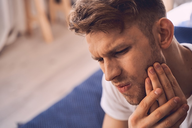 Suffering pain. sad bearded male pressing lips while touching his cheek, having problems with teeth