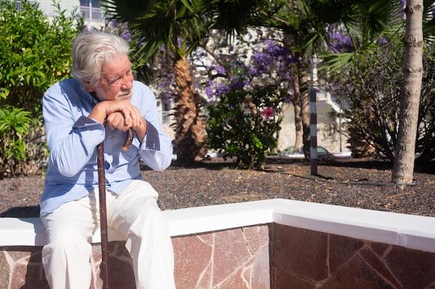 足の痛みのために棒を使用して屋外に座っている悲しい年配の男性に苦しんでいます