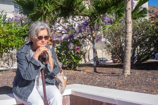 Страдания грустной пожилой женщины, сидящей на открытом воздухе с помощью палки от боли в ногах