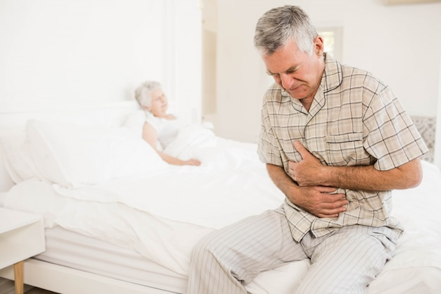 Suffering senior man holding his belly at home