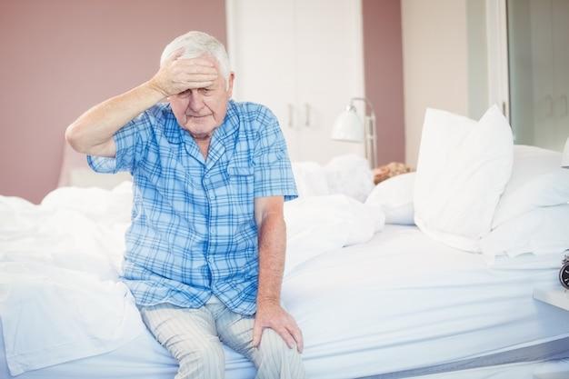 Suffering senior man holding his head st home