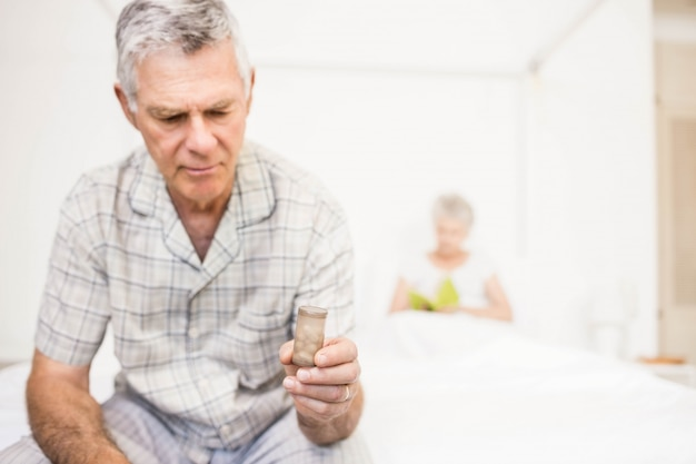 Suffering senior man taking pills at home