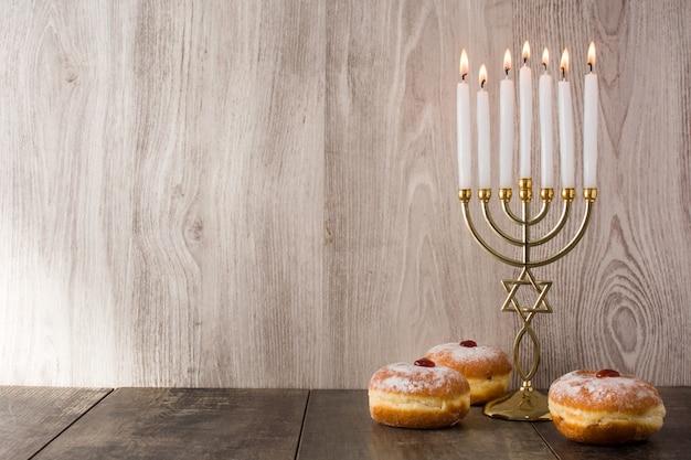 ユダヤ人のハヌカ本枝の燭台と木製のテーブルにsufganiyotドーナツコピースペース