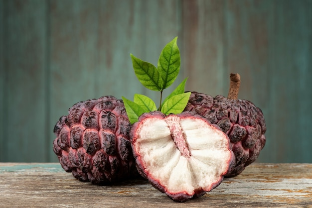 Sugar apple or annona squamosa fruits on an old wood background.