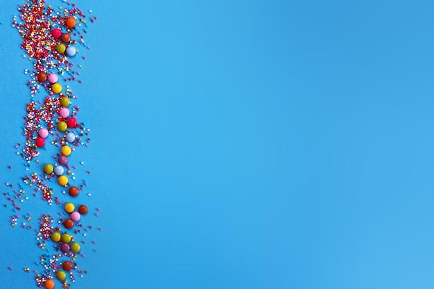 青い背景に分離された円の形でカラフルな振りかける砂糖焼き。休日のコンセプト。コピースペース