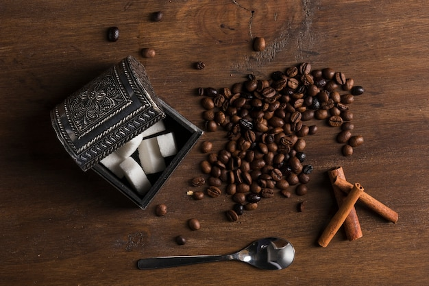 Sugar bowl and coffee beans near cinnamon sticks and spoon