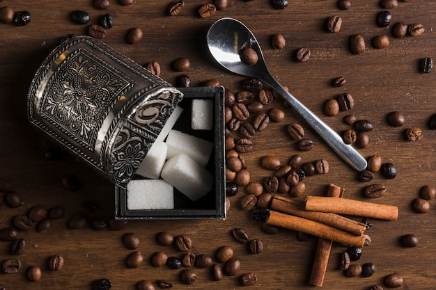 Sugar bowl near cinnamon sticks, spoon and coffee beans