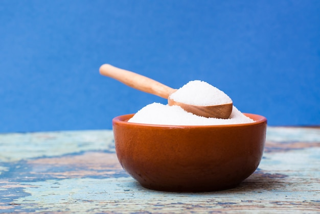 Sugar in a bowl and in a wooden spoon on a wooden table