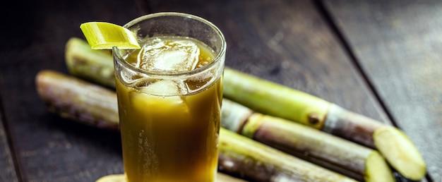 Сок сахарного тростника, сладкий зеленый сок, богатый акарози, на деревенском деревянном столе