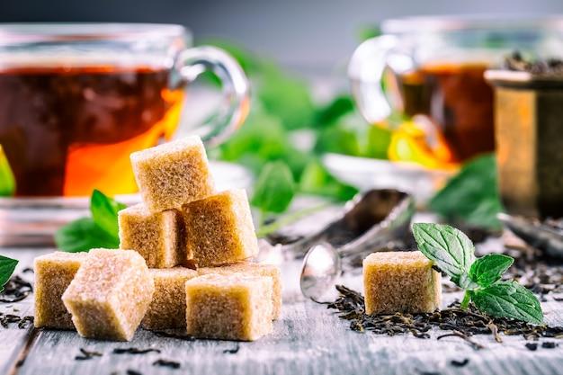 Сахар. тростниковый сахар. куча кубиков тростникового сахара заделывают макросъемку. чай в стеклянной чашке, листья мяты, сушеный чай, нарезанный лайм, тростниковый коричневый сахар