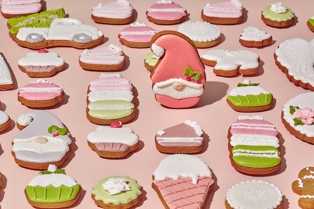 ピンクの背景に生姜クッキーの中で砂糖でコーティングされたジンジャーブレッドノーム