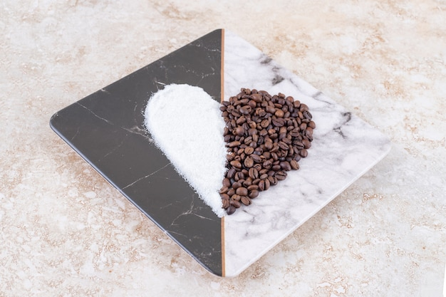 Sugar and coffee beans arranged into a heart shape on a marble plate
