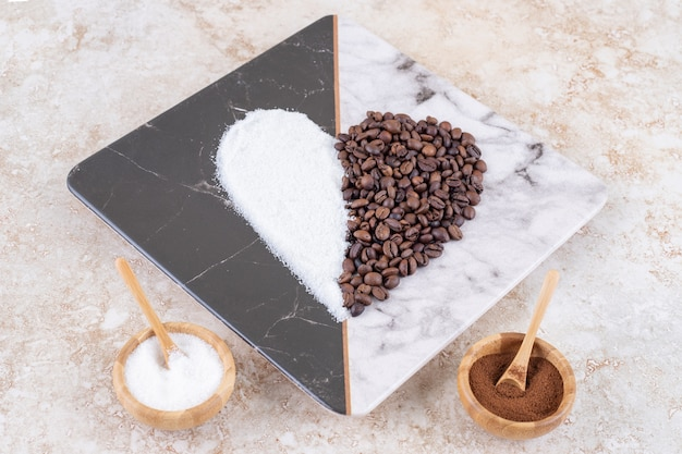 Sugar and coffee beans in small bowls and arranged into a heart shape on a marble plate