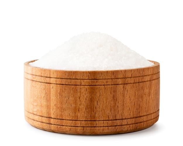 白い背景の上の木の板のクローズアップで砕ける砂糖。孤立