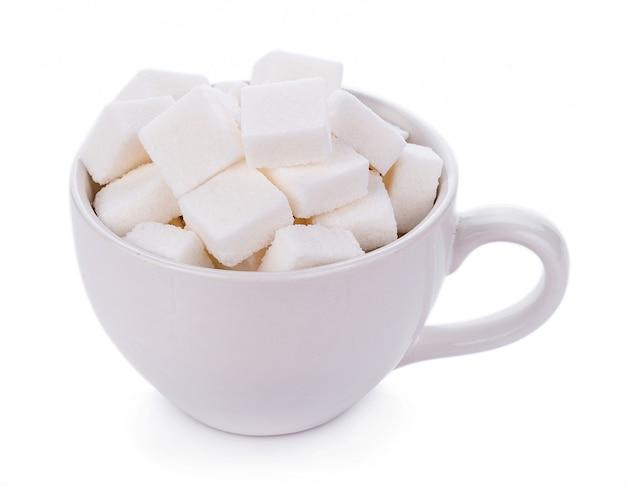 Кубик сахара в чашке на белой стене