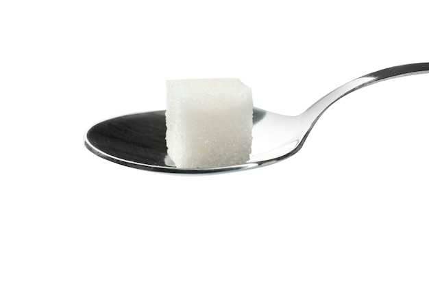 Sugar cube in spoon on white