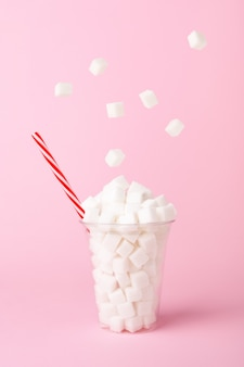Sugar cubes falling into glass on pastel pink