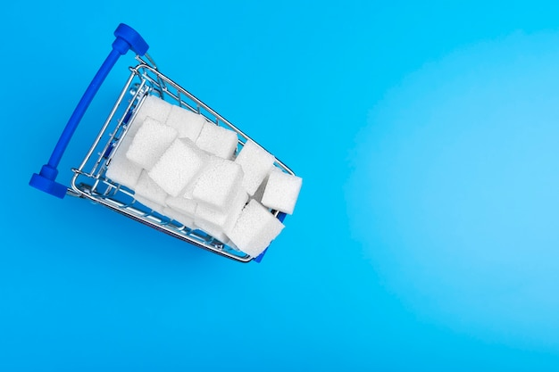 Sugar cubes in the shopping cart isolated on blue background.