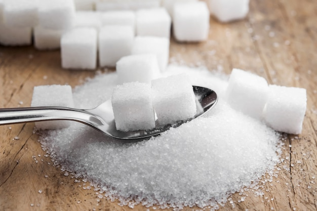 Sugar cubes in spoon on table wood background