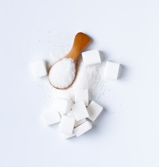 Sugar cubes and sugar in spoon. white sugar on white background. different sugar