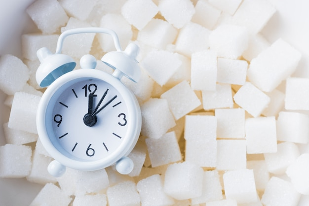 Кубики сахара, сладкий пищевой ингредиент и будильник