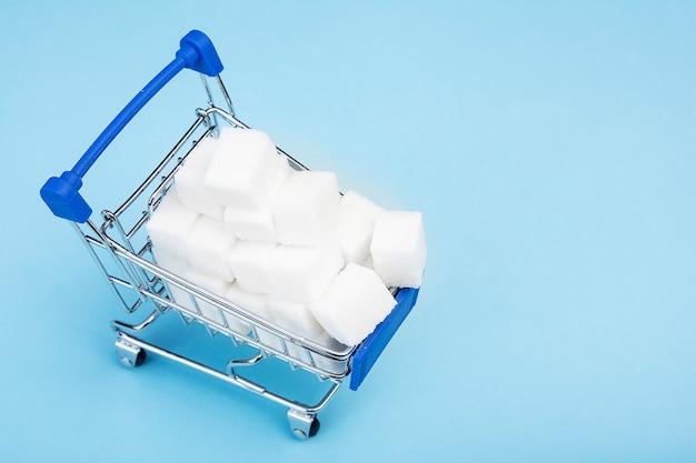 Sugar cubes. white sugar in the shopping cart on blue