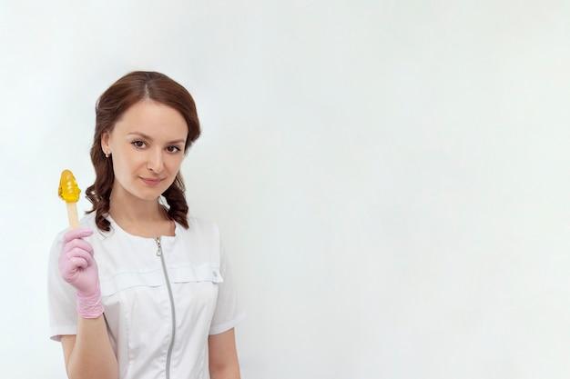 Косметическая процедура с сахарной депиляцией, шугаринг, красивая девушка, мастер держит в руках сахарную пасту.