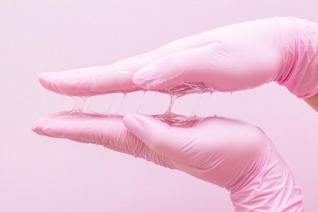 Sugar for depilation in hands in pink gloves on pink