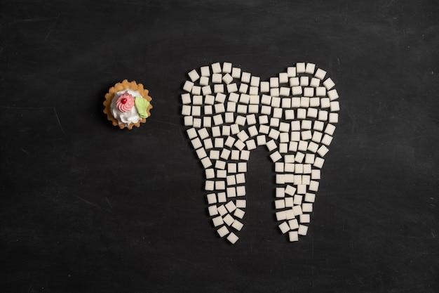 砂糖が歯のエナメル質を破壊する虫歯を導くホワイトシュガーキューブシェイプフォーム歯ブラウンシュガーカリエス黒の背景ヘルスケアと医学口腔病学の概念甘い食べ物が歯を破壊する
