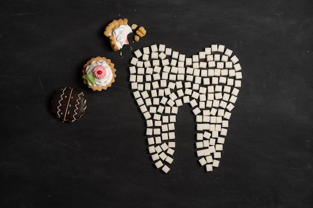 Sugar destroy tooth enamel leads tooth decay  white sugar cubes shape form tooth brown sugar caries black background healthcare and medicine stomatology concept sweet food destroy teeth