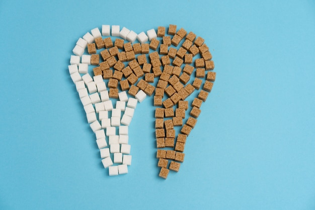 Sugar destroy tooth enamel leads tooth decay  white sugar cubes shape form tooth brown sugar caries blue background health care and medicine stomatology concept sweet food destroy teeth