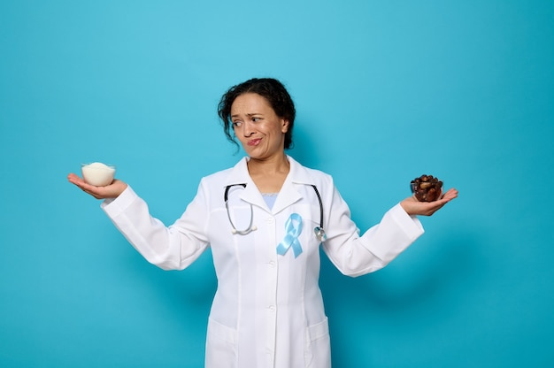 Sugar and diabetes concepts for world diabetes awareness day. pretty female doctor wearing blue ribbon holding a bowl with refined white sugar in one hand and ripe sweet dates in the other. copy space