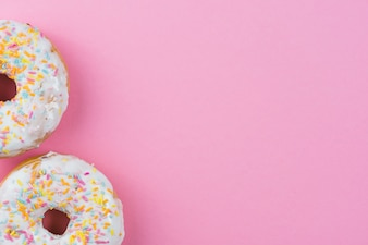 Sugar donuts with chocolate glaze and sprinkles on pink background