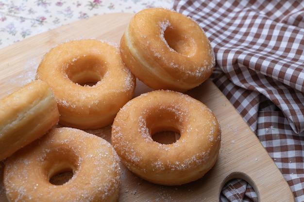 Sugar donuts on wooden board