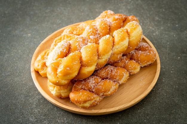 Сахарный пончик в форме спирали на деревянной тарелке