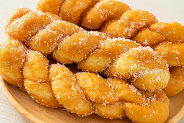 Сахарный пончик в форме спирали на деревянной тарелке Premium Фотографии