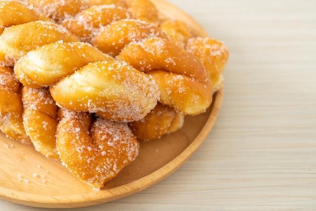 Sugar doughnut in spiral shape on wooden plate