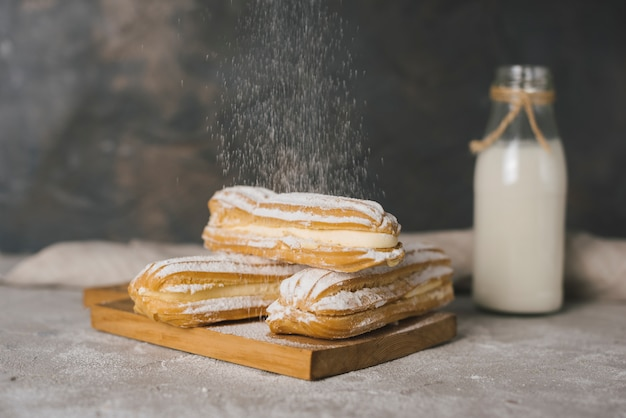 Sugar dusting on eclair over the wooden chopping board