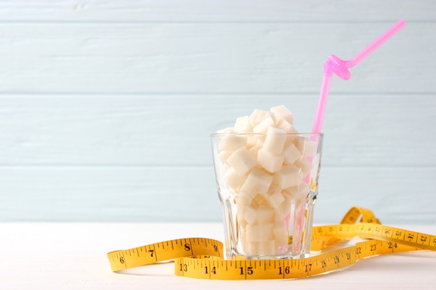 Sugar in a glass and measuring tape on a colored background