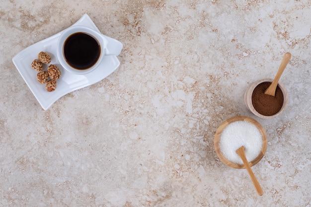 Zucchero, polvere di caffè macinato, una tazza di caffè e arachidi glassate