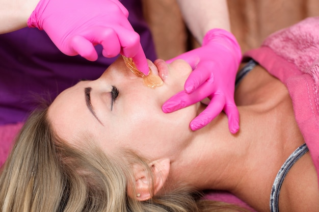 Сахарная эпиляция с женского тела. восковая эпиляция спа-процедура. процедура косметолога женского пола. усы.