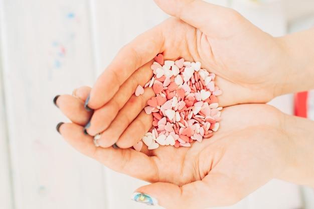 Сахарные сердечки в руках девушки